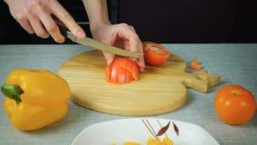 Flickan med en kniv klipper en röd tomat arkivfilmer