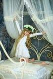 Flickan med en krans från vita rosor Arkivfoton