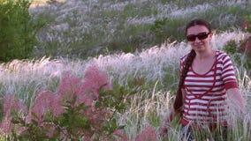 Flickan med en lång flätad tråd i solglasögon lager videofilmer