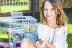 Flickan med en liten hamster gömma i handflatan in Arkivfoton