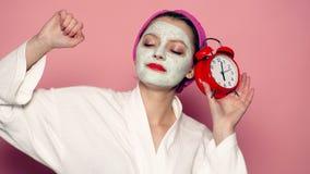 Flickan med en maskering på hans framsida rymmer en klocka i hans hand på en rosa bakgrund Begrepp av hudomsorg lager videofilmer