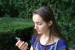 Flickan med en mobil ringer Arkivfoto