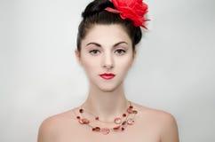 Flickan med en röd blomma Royaltyfri Bild