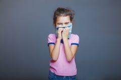 Flickan med en rinnande näsa tryckte på näsduken till henne royaltyfri fotografi