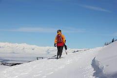 Flickan med en snowboard går bort längs lutningen Royaltyfri Foto