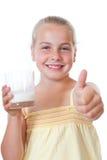 Flickan med ett exponeringsglas av mjölkar och tummar upp Arkivfoton