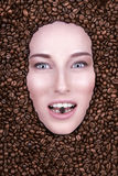 Flickan med ett leende badade i kaffebönor Royaltyfri Bild