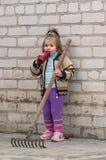 Flickan med ett trädgårds- krattar Royaltyfria Bilder