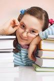 Flickan med exponeringsglas och en radda bokar Arkivbild