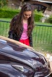 Flickan med fällda ned ögon, beskrev utomhus, medan reflektera i en tappningbil arkivfoto