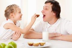 Flickan med fadern har en frukost royaltyfri foto