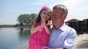 Flickan med farfadern på gatan har gyckel Lite visar flickan en farfar, dem skrattar 4K l?ngsam mo stock video