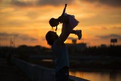 Flickan med farsan som går i solnedgångkontur royaltyfri bild