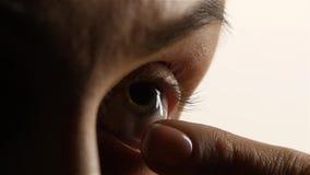 Flickan med fattig vision sätter linsen och exponerar close upp Vit bakgrund långsam rörelse stock video