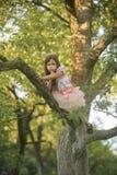 Flickan med fingershow hyssjar tystnadtecknet, gest på träd Arkivbild
