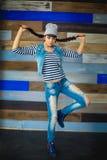 Flickan med flätade trådar i jeans passar Royaltyfri Fotografi