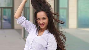 Flickan med flödande hår står nära modern byggnad stock video
