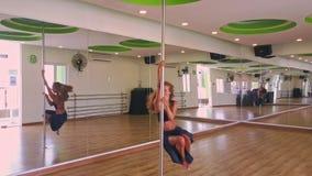 Flickan med frodigt hår dansar på Pole i repetitionen Hall lager videofilmer