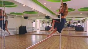 Flickan med frodigt hår klättrar upp och rymmer Pole i mitt av Hall lager videofilmer