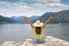 Flickan med händer tycker om upp en Kotor för sommarferie fjärd royaltyfria bilder