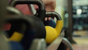 Flickan med härligt spikar lyfter viktcloseupen från hyllan i ultrarapid lager videofilmer