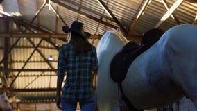 Flickan med hästen står i stallen arkivfilmer