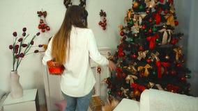 Flickan med hörlurar som lyssnar till musik och, sätter gåvor under julgranen arkivfilmer