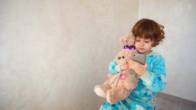 Flickan med kanin klickar nyfiket smartphonen Royaltyfri Fotografi
