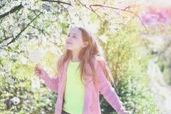 Flickan med klubbagodisen som in går, parkerar på att blomstra bakgrund arkivfoton