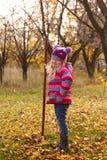 Flickan med krattar på trädgården Royaltyfri Fotografi