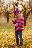 Flickan med krattar på trädgården Arkivfoton