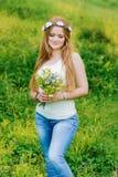 Flickan med långt blont hår ser buketten royaltyfri fotografi