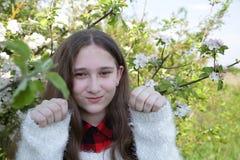 Flickan med långt hår håller nävar upp på bakgrunden av blomningträd på en mjuk suddig bakgrund royaltyfri foto