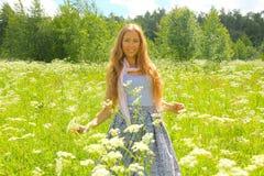 Flickan med långt hår ler i det gröna fältet Royaltyfri Bild