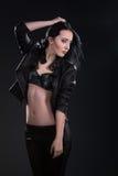 Flickan med långt hår på svart bakgrund arkivfoton