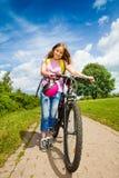 Flickan med långt hår rymmer hennes cykel och hjälm Arkivbild