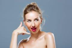 Flickan med ljus makeupvisning kallar mig gesten över grå bakgrund Royaltyfri Foto