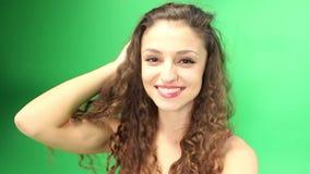 Flickan med lockigt hår som omkring rotera den gröna skärmen, går pro- lager videofilmer