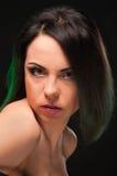 Flickan med mörkt hår på svart bakgrund royaltyfria foton