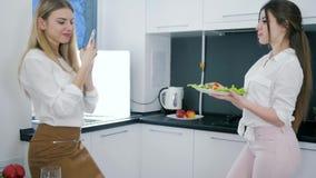 Flickan med mobiltelefonen tar bilder av flickväninnehavmaträtten med sallad i händer på kök arkivfilmer