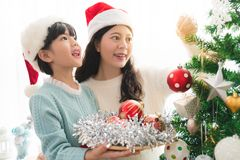 Flickan med mumen dekorerar en julgran Arkivfoton