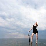 Flickan med paraplyet plattforer på vattnet Arkivbilder