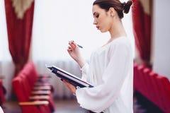 flickan med pennan i hennes hand håller ögonen på dokument arkivbild