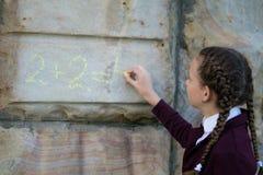 Flickan med råttsvansar, skrev ett matematiskt exempel på en stenvägg schoolgirl royaltyfri bild
