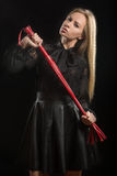 Flickan med rött läder piskar Royaltyfri Fotografi