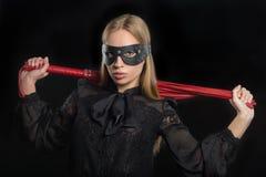 Flickan med rött läder piskar och maskerar BDSM Royaltyfri Fotografi