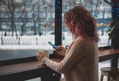 Flickan med rött lockigt hår i en vit tröja sitter i ett kafé mitt emot ett stort fönster royaltyfri foto