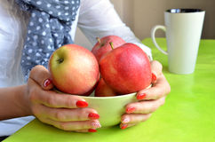 Flickan med rött spikar på som henne, rymmer fingrar den gröna bunken full av äpplen royaltyfri fotografi