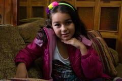 Flickan med rosa färger klår upp i en soffa 3 Arkivfoto