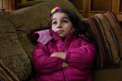 Flickan med rosa färger klår upp i en soffa 1 Fotografering för Bildbyråer
